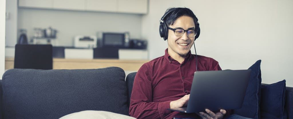 Man sitting on his couch, smiling and reading on his laptop about the benefits of a savings account