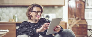 Woman sitting on her couch at home, smiling and reading on her tablet about the best loans for good credit
