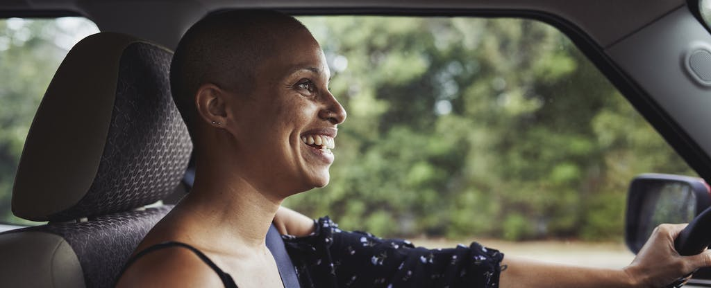 Woman smiling and driving her new car