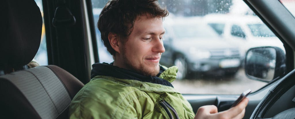 Young man wearing a green rain jacket sitting inside his car and checking his phone to see if his insurance covers windshield cracks