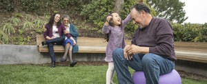 Young child playing in the yard with her grandfather, her mother and grandmother looking on while they discuss setting up an education savings account