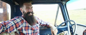 Smiling bearded man sits in his truck that he bought with a golden 1 auto loan