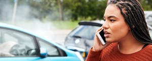 Young woman in a car accident, standing on the side of the road on her phone asking what happens when you total your car