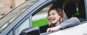 Smiling young woman driving her car that's insured with GEICO auto insurance