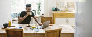 Man sitting at his kitchen table, eating breakfast and reading on his laptop about the best personal loans for fair credit