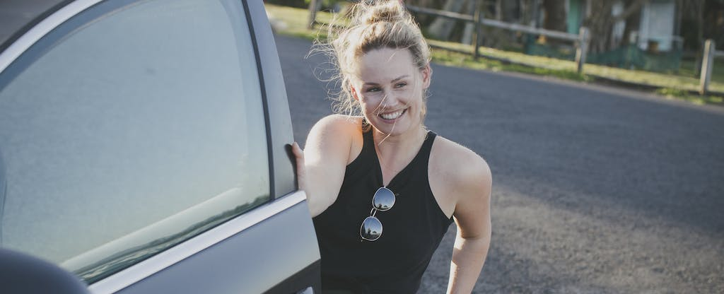 Woman smiling as she's getting into her car