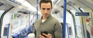 Man standing on train, holding coffee and cell phone and looking up Continental Loans
