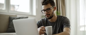 Young man at home drinking coffee and looking at trip cancellation insurance
