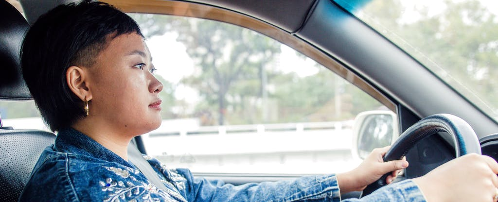 Woman driving her car, insured with Liberty Mutual Auto Insurance