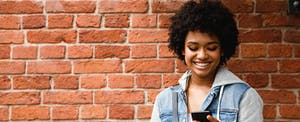 College student leaning against a wall, smiling and reading about savings accounts on her phone