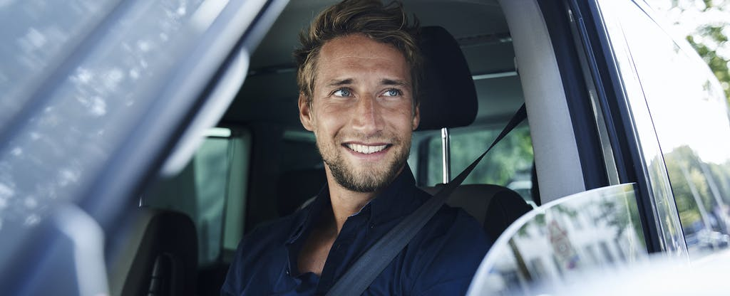 Young man looking out car window and smiling