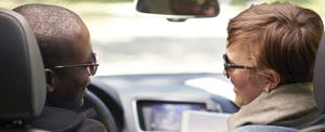Couple in a car together, while the passenger is reading aloud about personal injury protection on her tablet