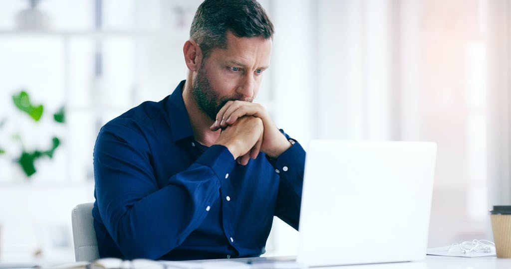Man sitting at computer looking up average funeral cost