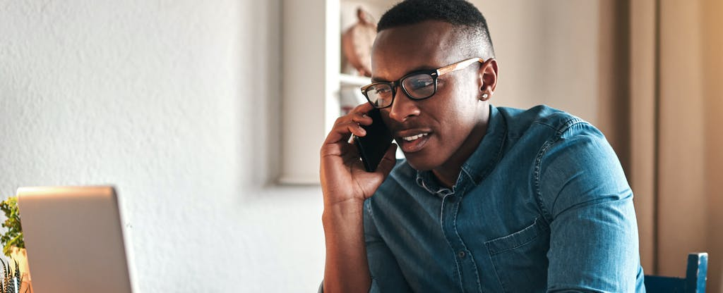 Young man at home on cellphone, contacting a credit bureau to get a copy of his credit report