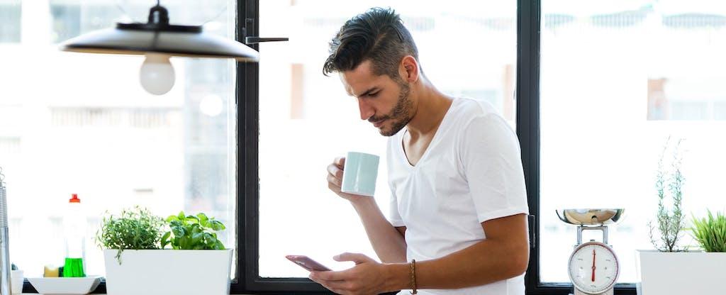 Un hombre mira su teléfono en la cocina