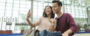 una pareja se toma una selfie juntos en el aeropuerto