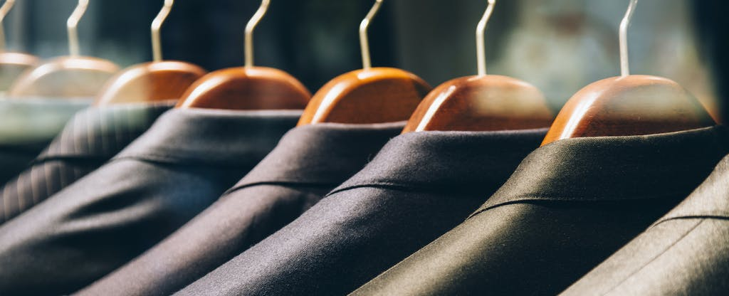 Men's suit jackets hanging in a clothing store