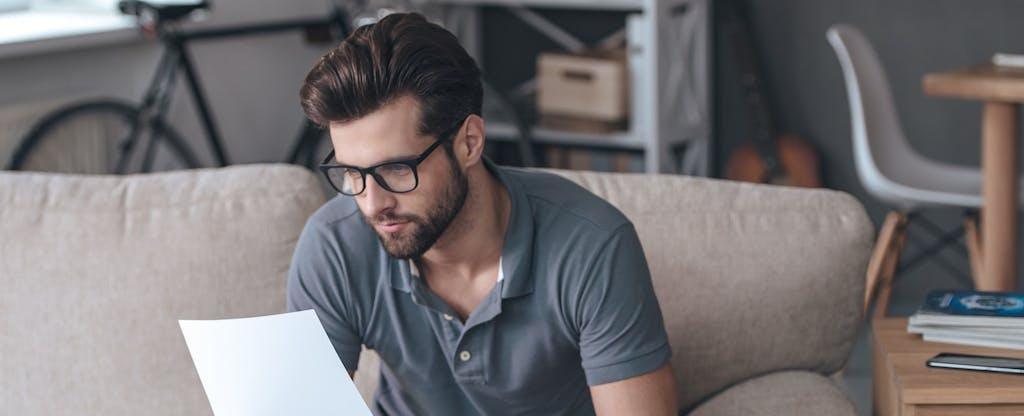 un hombre mira el papeleo tratando de entender sus opciones porque no tiene un puntaje de crédito