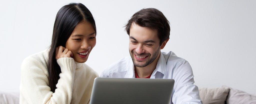 un hombre y una mujer miran una computadora portátil juntos sonriendo