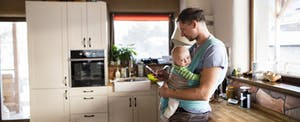 Young father at home in the kitchen holding smart phone, looking up property tax relief, baby son in sling
