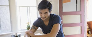 Man at home wondering if the coronavirus will affect his credit