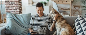 Young man sitting on sofa with his dog and looking up the average credit score on his phone
