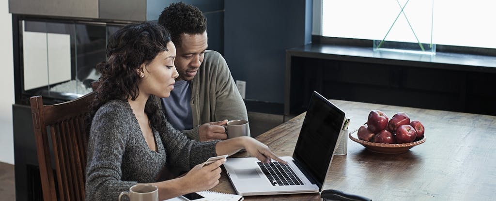 Man and woman sitting together at their kitchen table, looking at a laptop while considering a Credit Direct loan