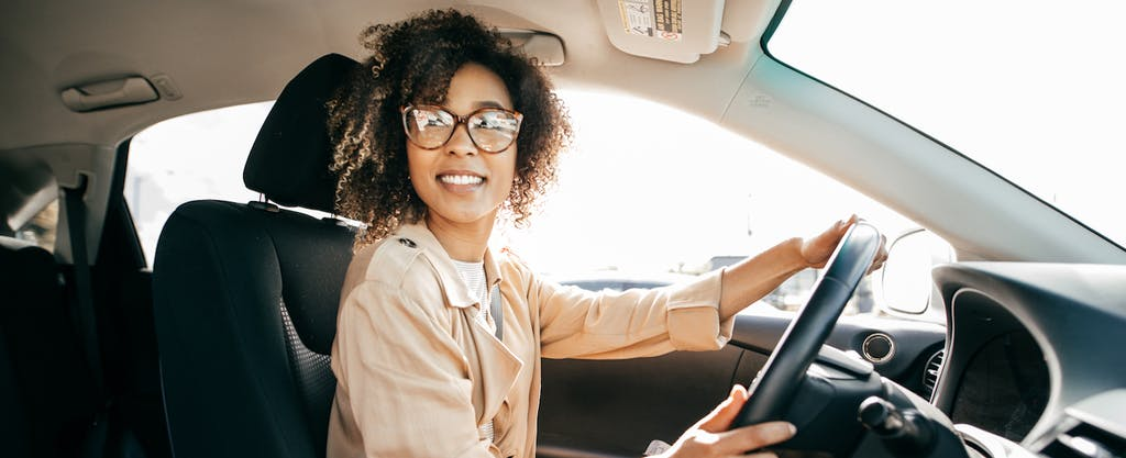 Smiling young woman wearing glasses driving a car