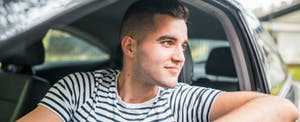 Man driving his car, smiling and looking out the window