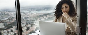 Businesswoman working on her laptop, reading about small business relief