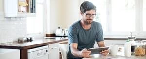 Man sitting in kitchen with digital tablet, looking up trip cancellation insurance