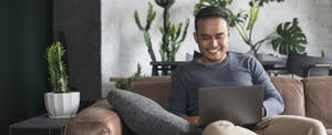 Man sitting at home on his couch, reading on his laptop about tax form 5498