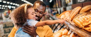 Man and daughter shopping together in a grocery store, where he plans to use his Amex Everyday Preferred card