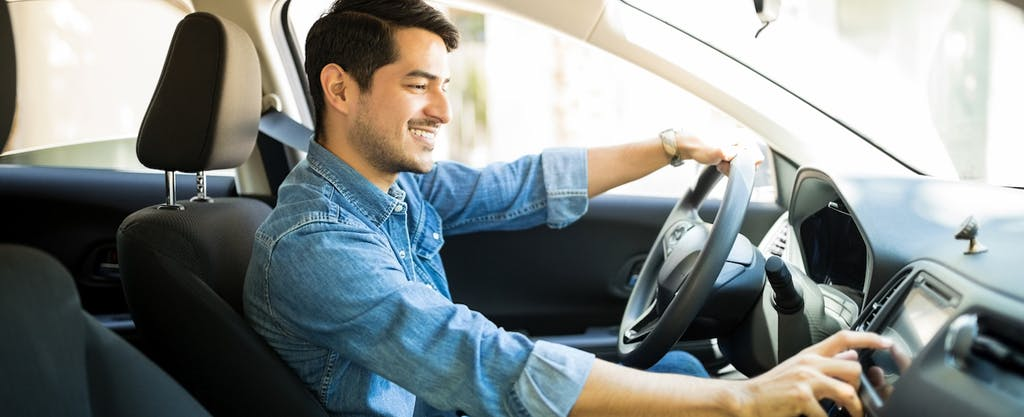 Man turning on the radio in his car that he insured with amica auto insurance