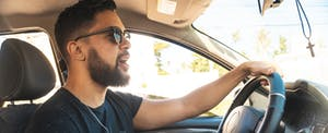 Young man wearing sunglasses driving his car and singing