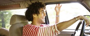 Happy man driving car that he insured with farmers auto insurance