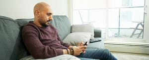 Man sitting on couch at home, looking up Fig Loans on his cellphone