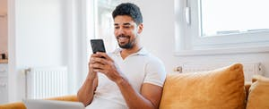 Man sitting on sofa at home with cellphone, looking up how to save money