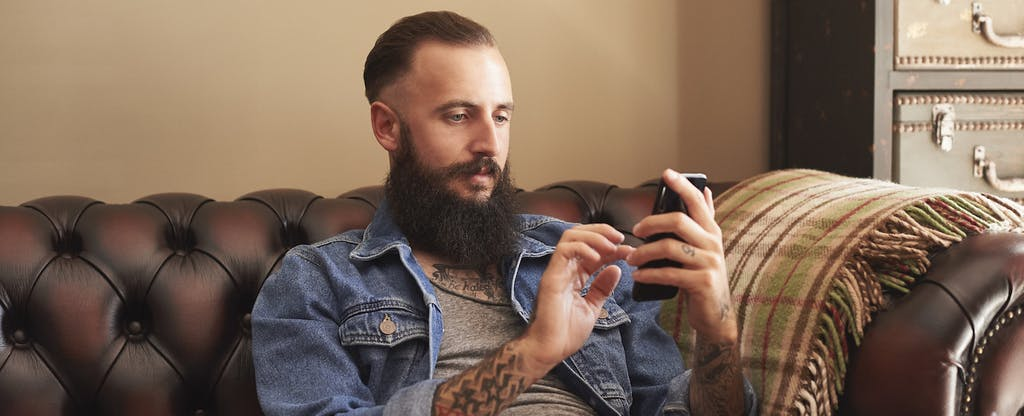Young man sitting on couch at home, looking up what is a bad credit score on his cellphone