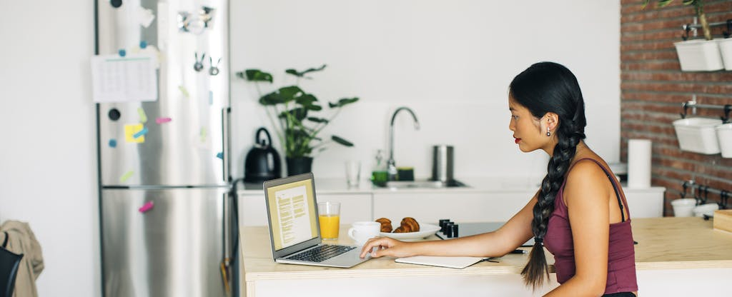 Woman working on laptop in kitchen at home, filling out a W-9 tax form