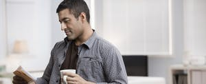 Man holding bills and looking up short term loans on his cellphone
