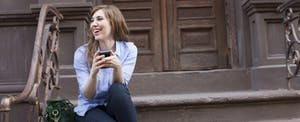 Woman sitting on the steps outside her apartment, smiling as she uses the Brigit app on her phone