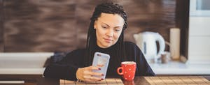 Young woman on cellphone, looking up elan financial on her credit reports