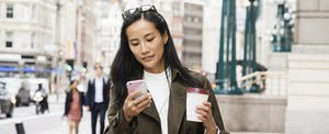 Woman walking on city street with coffee, looking up eos cca credit reports on her cellphone