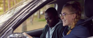 Woman driving a car with her partner in the front seat, smiling as they discuss their Metromile Insurance coverage