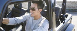 Young man wearing sunglasses and driving his Jeep with the top down