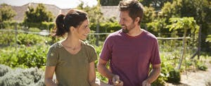 Man and woman standing outside in their garden, discussing getting a loan from Possible Finance