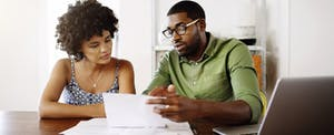 Young couple looking at why tbom is on their credit report