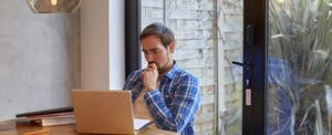 Man sitting at kitchen table with laptop, looking up texas payday loans