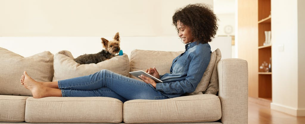 woman on couch cancelling her trip with credit card with trip cancellation insurance
